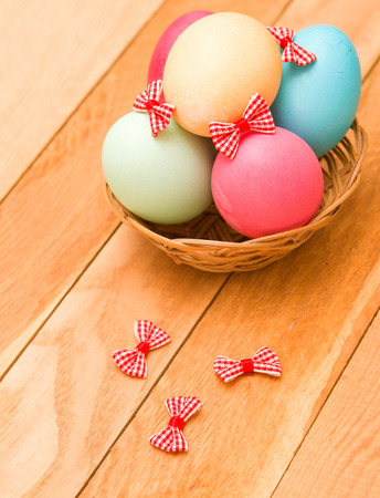Easter eggs in a wicker basket on a wooden background