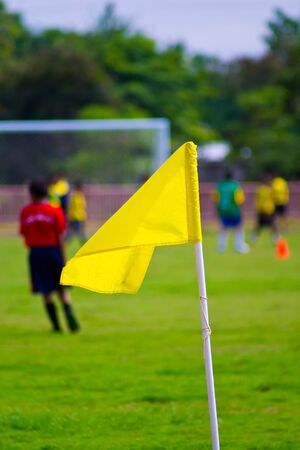 winning pitch: Yellow flag on a football field Stock Photo