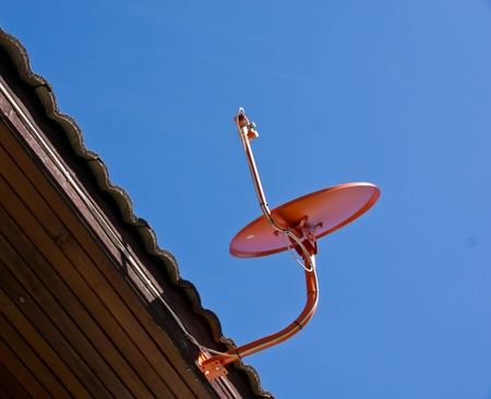 Orange satellite dish attached to the roof  photo