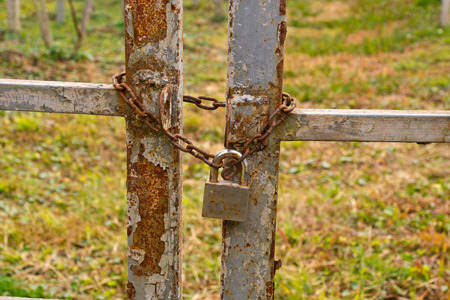 padlocked: Old rusty padlock with a chain padlocked closed doors  Stock Photo