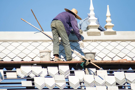 Two men were repairing the roof of the white tiles.