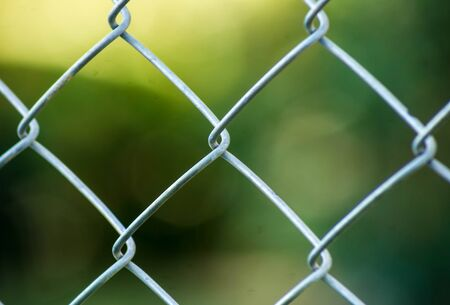 Closed up metal fence is Bokeh green