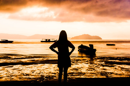 Woman standing facing the sea watching the sunset. Stock Photo