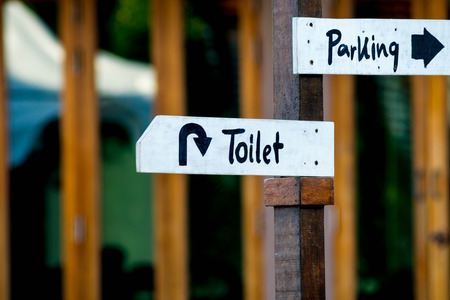 closed up Toilet and Parking wooden sign Stock Photo