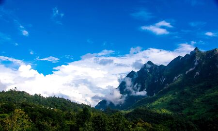 White clouds float over the mountains with blue sky Stock Photo