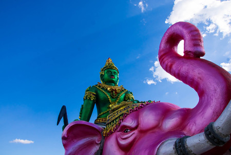 The green Indra statue sits on a pink elephant behind the clouds and the sky. Stock Photo
