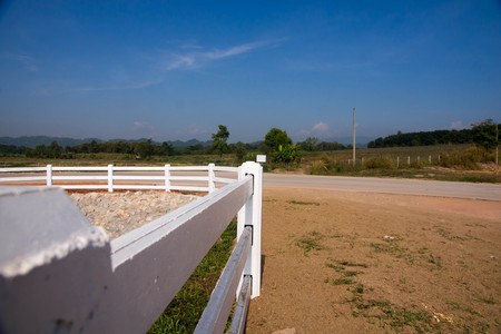 The white fence in the countryside has mountains and blue sky