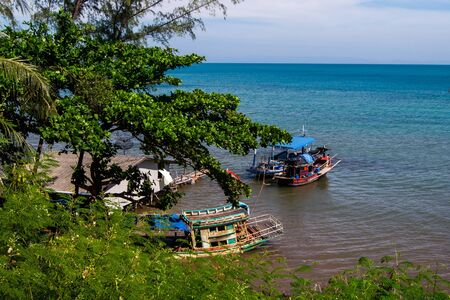 Thai fishing boats parked in the sea ,Have a house near Stock Photo