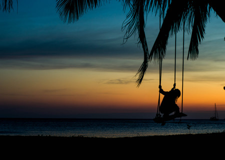 Some people are playing swings by the sea ,silhouette