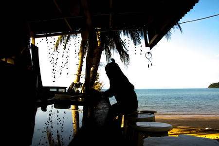 woman sitting at a beachside bar in the daytime ,silhouette