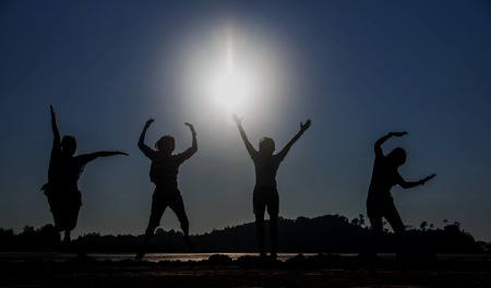 Four people jumping at the seaside ,silhouette Image Stock Photo