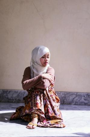Pretty Islamic girl sitting  lonely Stock Photo