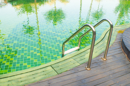 green swimming pool with teak wood flooring stripes summer vacation