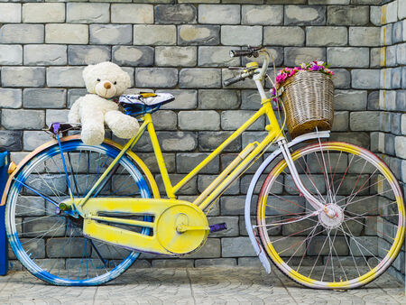 fancy bicycle with cute bear doll at brick wall