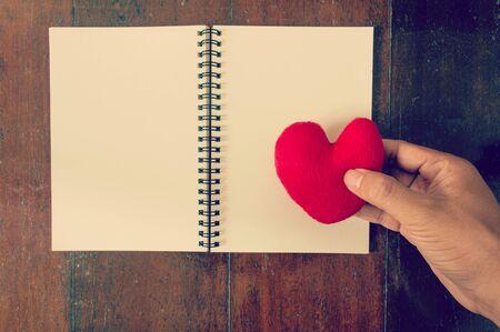 Hand legte das Herz auf Notizblock gefiltert Wirkung