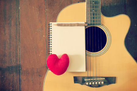 Notebook and wooden pencil with heart on guitar,Writing music filtered effect Stock Photo