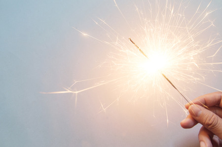 man's hand holding a sparkler on the white background