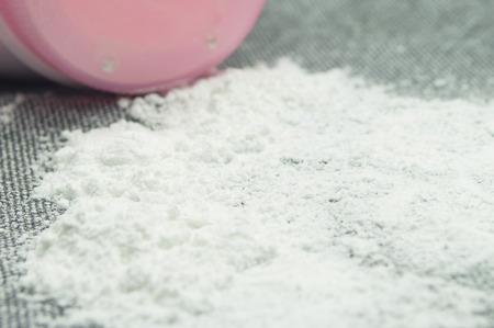Baby talcum powder container on gray fabric background Foto de archivo