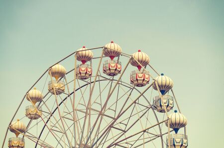 low angles: ferris wheel against blue sky, vintage filter effects Stock Photo