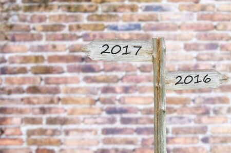 Wooden Blank Sign With Text 2017 and 2016, Over Blurred brick wall Image for New year 2017 Concept. Stock Photo