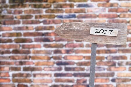 Wooden Blank Sign With Text 2017 , Over Blurred brick wall Image for New year 2017 Concept. Stock Photo