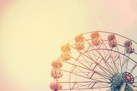 Ferris wheel on sky background with sunlight retro effect image