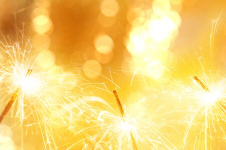 Gold light sparkler with bokeh de focused blurred background,New year celebration background Stock Photo