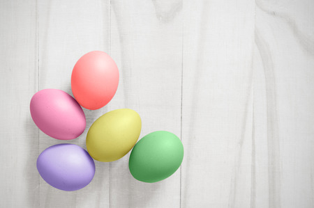 Vintage colorful easter eggs on white wood table background with clipping path of the eggs Lizenzfreie Bilder