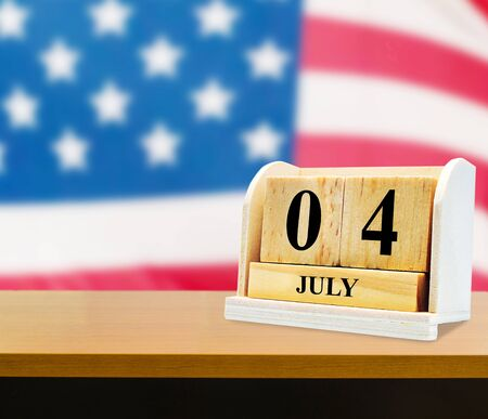 Cube shape calendar for July 04 on wooden table on usa flag background