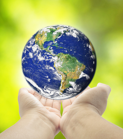 holding planet Earth in hands against  green grass spring background Elements of this image furnished by NASA