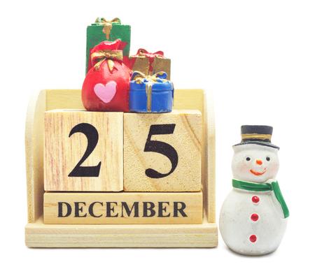 Hölzerner Kalender am 25. Dezember mit Weihnachten und neuem Jahr verzieren den Schneemann und die gifbox, die mit Beschneidungspfad lokalisiert werden, für Weihnachts- und guten Rutsch ins Neue Jahr-Dekoration Konzept feiern.