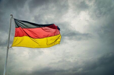 Eine deutsche Flagge vor dunklen Wolken Hintergrund Lizenzfreie Bilder