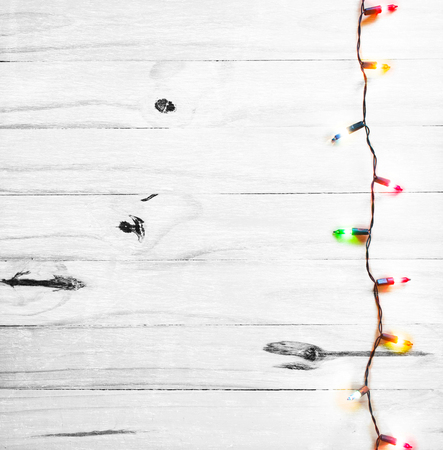 Christmas lights on white wooden  background with copy space for your text