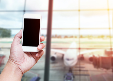 A man hand holding empty screen of smart phone blurred photo airport terminal background with screen clipping path of phone include.