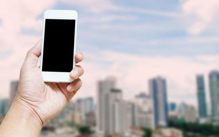 Eine Mannhand, die leeren Schirm des intelligenten Telefons hält, verwischte städtisches Hintergrundinternet-Internet des Sachekonzeptes mit Schirmbeschneidungspfad des Telefons schließen ein.