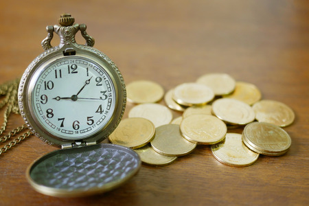 vintage golden pocket watch with stack  on wood table background.time money concept.