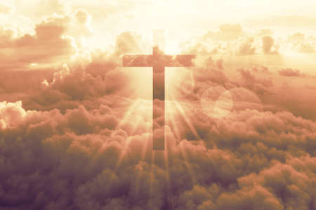 Christian cross appears bright in late sunset yellow sky background Stock Photo