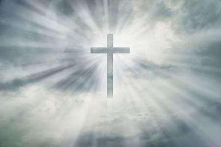 Christian cross appears bright on dramatic dark sky background Stock Photo