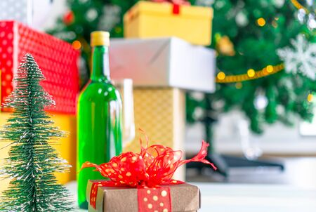 A gift box with a red bow placed next to a small Christmas tree in a white room decorated with bright, colorful lights makes it a delight for those who see it for Christmas and New Year's holidays.