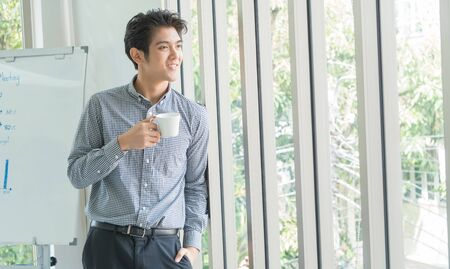 A 25-35 year old Asian man smiled happily and relaxed in a white office. He held a coffee cup and looked out.