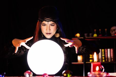 A black woman dressed as a witch performs a ritual in a mysterious, horrifying, and abrupt room. Crystal Ball shines.