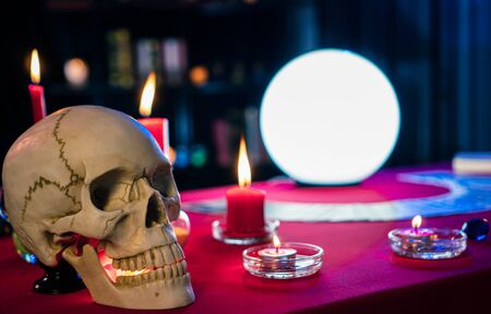 On the table covered with red carpet With a human skull and cards, paper, and talismans These items are used in performing evil magic rituals.