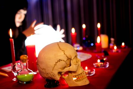 A black woman dressed in a witch-like dress with a skull placed side by side performed a ritual in a mysterious, horrible, and abrupt room. Crystal Ball emitted a glow. Stock Photo