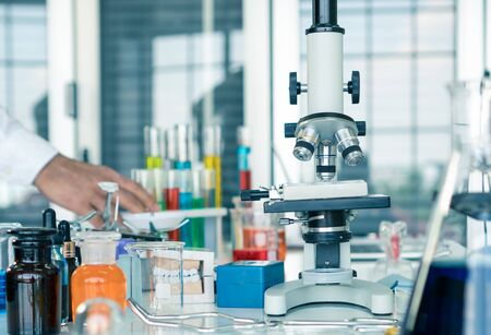 The microscope is located on the table in a scientist's laboratory and contains a glass tube containing many colored chemicals used in science research and experimentation.