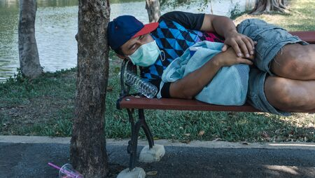 Asian homeless man wearing protective mask sleeping on a bench. Unemployed due to the impact of the spread of the virus.