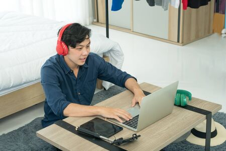 A young Asian man is reviewing a product via live streaming on social media. Online sales are freelance and can be done at home.