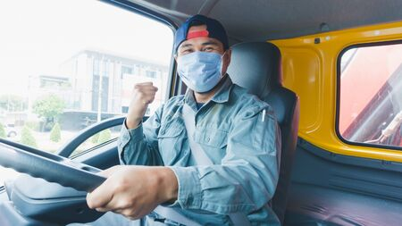 Close-up photos of Asian truck drivers wearing masks to protect against dust and the spread of the flu. Covid 19. Inside the car front.He holds a fist to fight an obstacle.