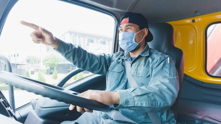 Close-up photos of Asian truck drivers wearing masks to protect against dust and the spread of the flu. Covid 19. Inside the car front.He is smiling and pointing forward.