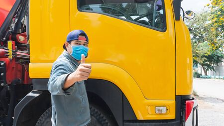 The truck driver, an Asian man, was standing at the door of the car. He put on a mask to prevent dust and prevent the spread of the virus.