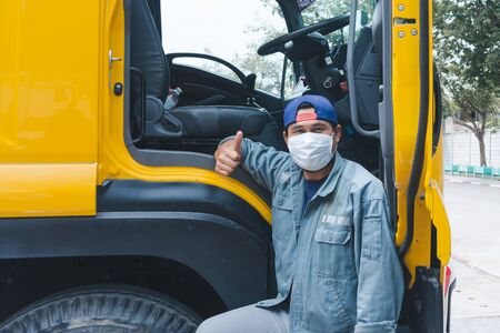 Close-up photos of Asian truck drivers wearing masks to protect against dust and the spread of the flu. Covid 19. Inside the car front Stock Photo